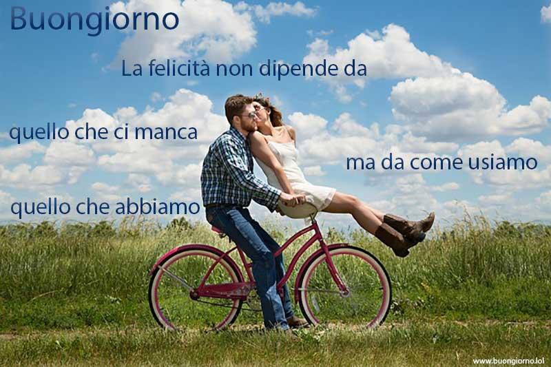 Una coppia felice che va in bicicletta sotto un cielo azzurro