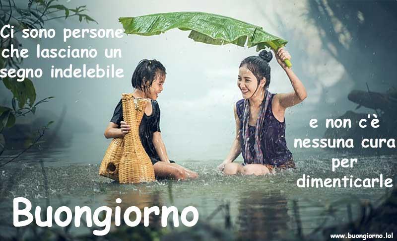 Una madre protegge sua figlia dalla pioggia con un foglia gigante