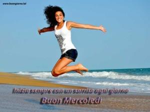 ragazza sorridente salta sulla spiaggia in riva al mare
